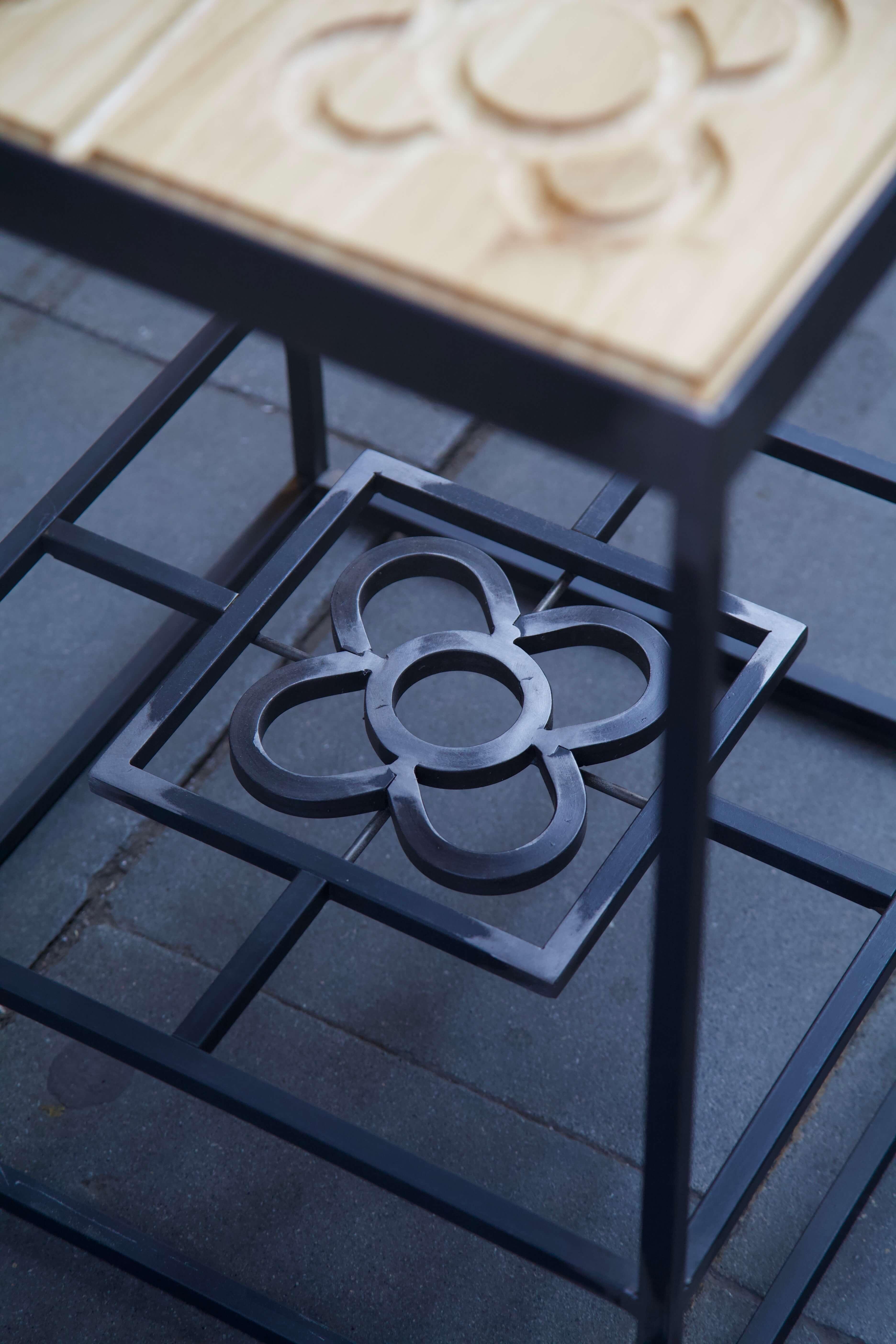 Detalle de la flor de la mesa hecha con estructura de hierro y panots flor de barcelona en madera